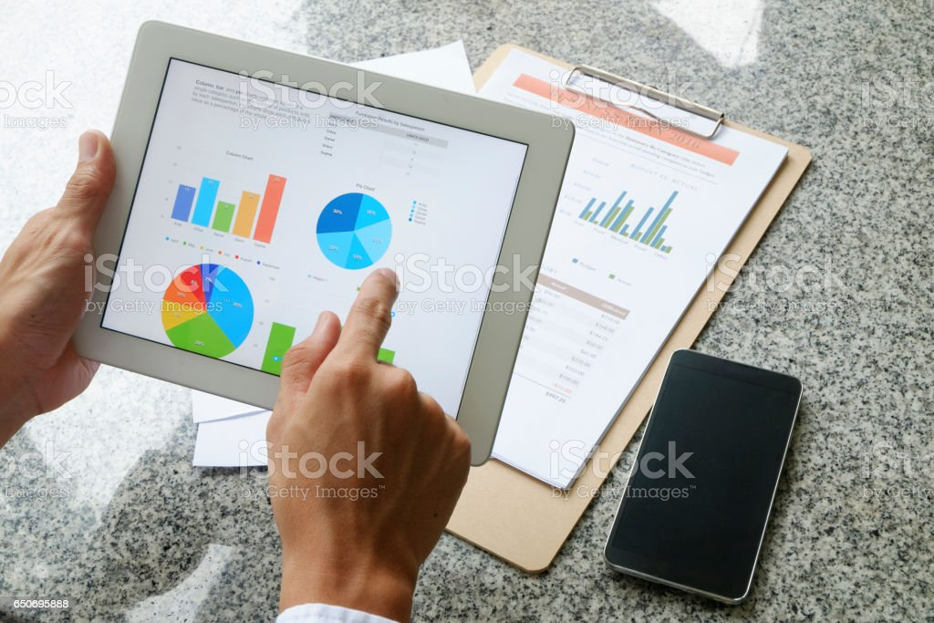 business man hold analyzing financial chart on tablet stock photo