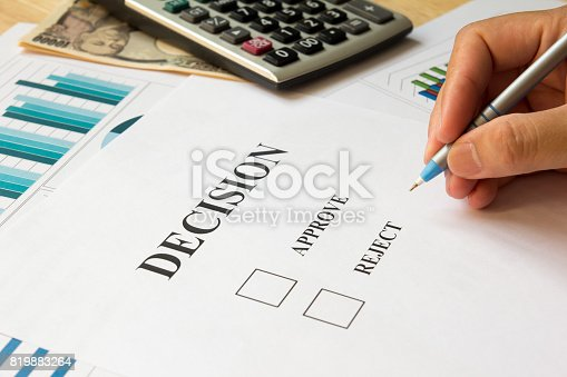 istock Business man hold the pen for decision on paper with calculator, financial graph, chart, japanese yen banknote background 819883264