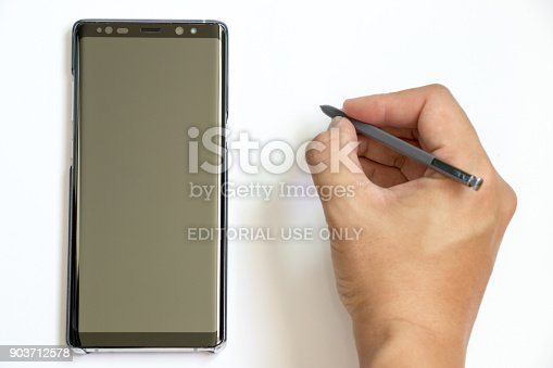 istock Business man hold the stylus to write at Samsung Galaxy Note 8 on white background. It is the flagship smartphone with android os. 903712578