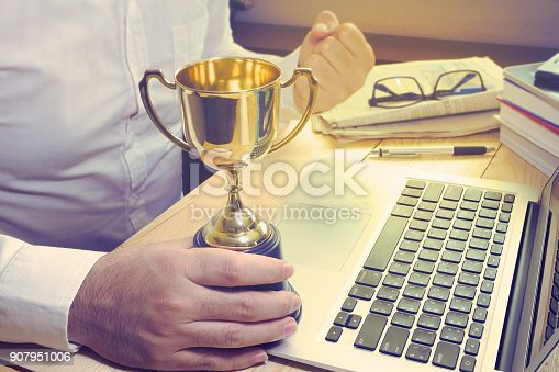istock Business man hold trophy and feel like a winner on his working table,finance concept. 907951006