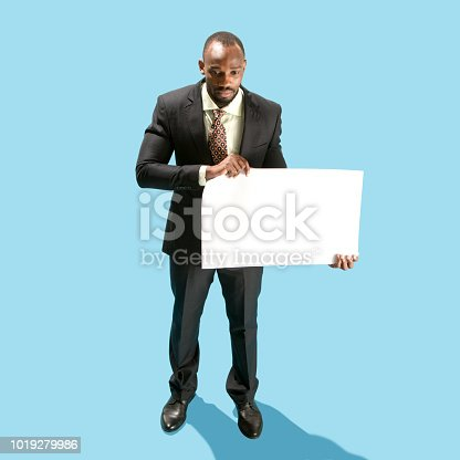 1048561956 istock photo Business man holding a blank banner isolated on blue background 1019279986