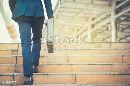 istock Business man holding a briefcase walking up the stairs in the routine of working with determination and confidence. 843564270