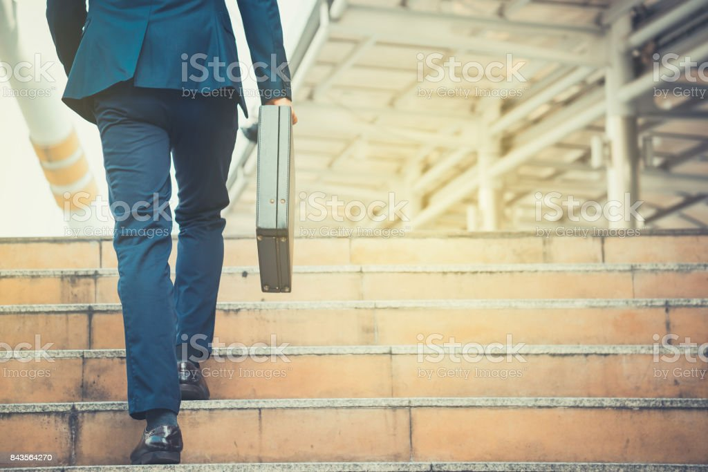 Business man holding a briefcase walking up the stairs in the routine of working with determination and confidence. stock photo