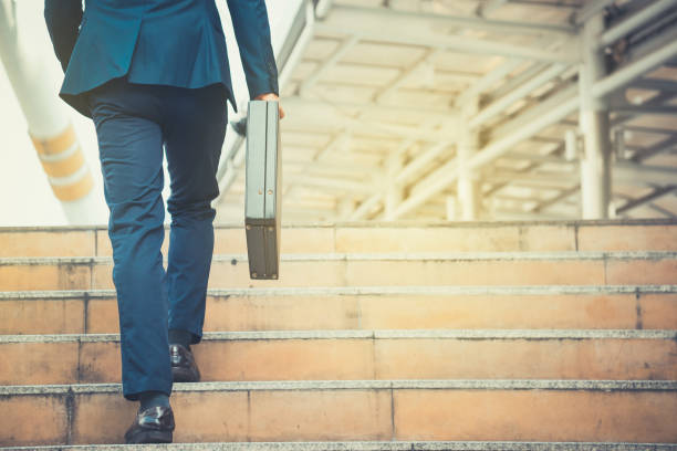 Business-Mann hält eine Aktentasche Treppensteigen in der Routine der Arbeit mit Entschlossenheit und Vertrauen. – Foto