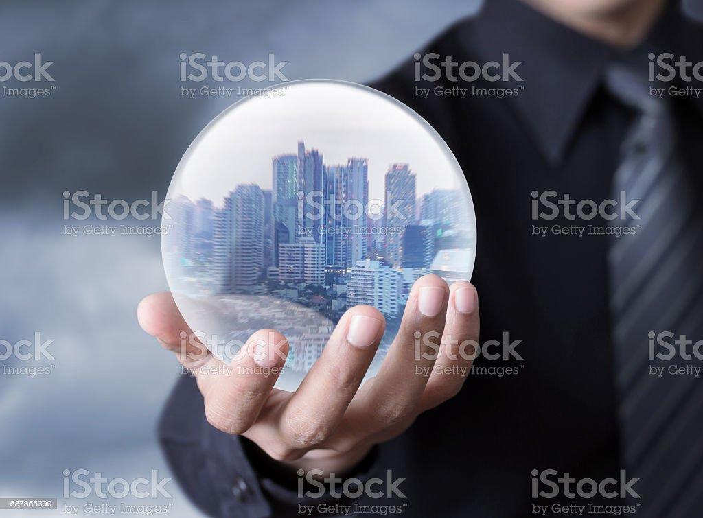 Hombre de negocios sosteniendo un ciudad dentro de una esfera - foto de stock