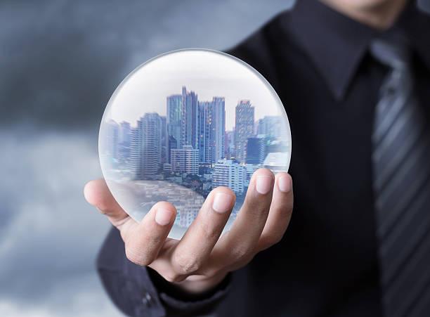 homme d'affaires tenant un ville à l'intérieur d'une sphère - boule de cristal photos et images de collection