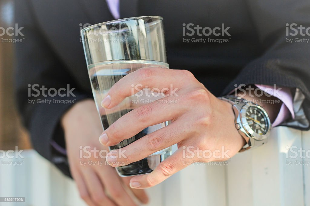 business man holding a glass of water stock photo