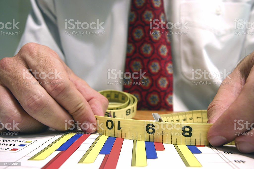 Business man holding a measurement tape over column charts royalty-free stock photo