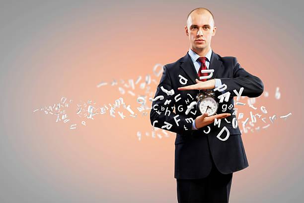 Hombre de negocios sosteniendo alarmclock - foto de stock