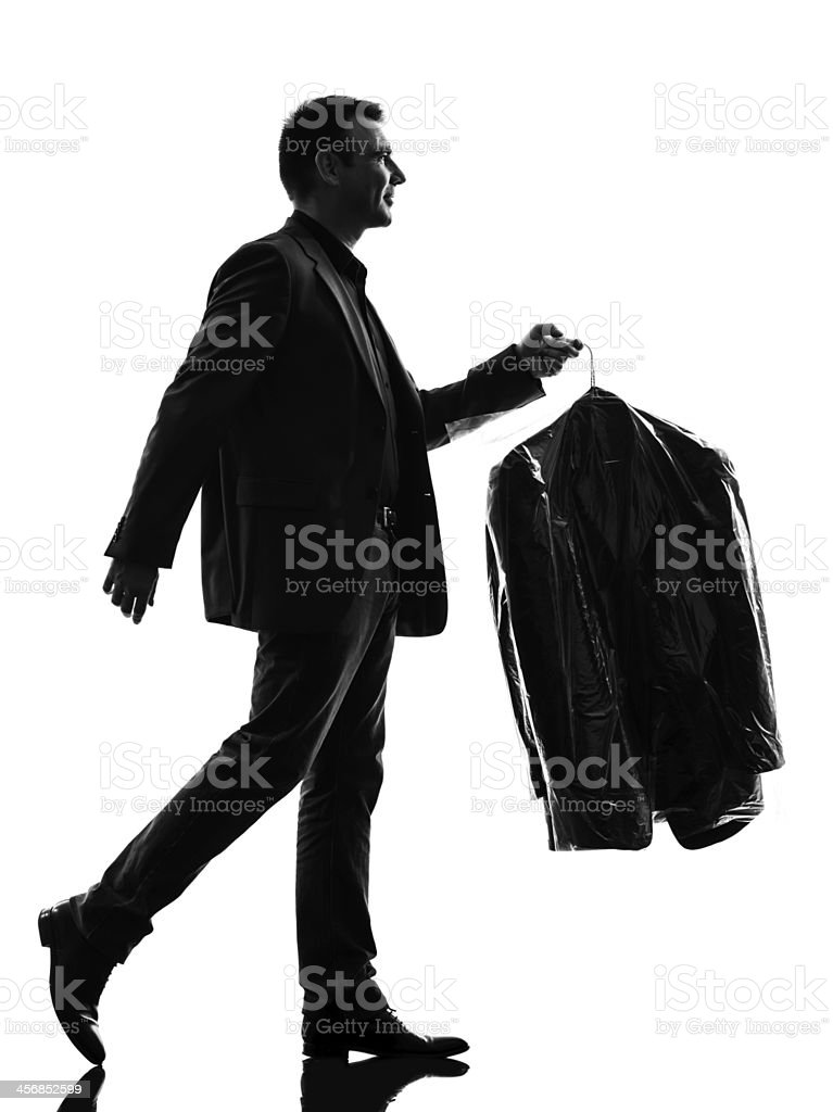 business man holding dry clean clothes silhouette stock photo