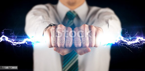 istock Business man holding electricity light bolt in his hands 1158773905