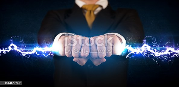 1152920014 istock photo Business man holding electricity light bolt in his hands 1190822802