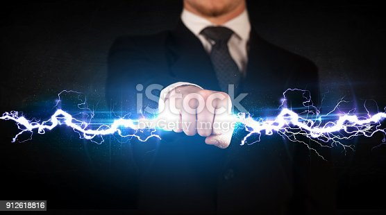istock Business man holding electricity light bolt in his hands 912618816