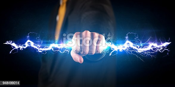 istock Business man holding electricity light bolt in his hands 948499014