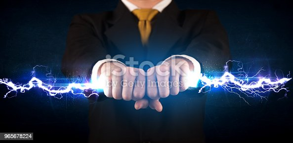 istock Business man holding electricity light bolt in his hands 965678224