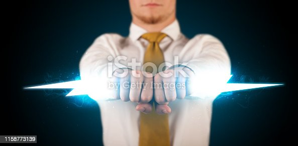 istock Business man holding glowing lightning bolt in his hands 1158773139
