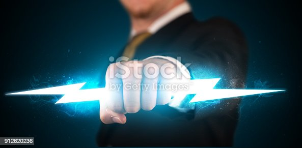 istock Business man holding glowing lightning bolt in his hands 912620236