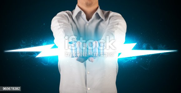 istock Business man holding glowing lightning bolt in his hands 965678382