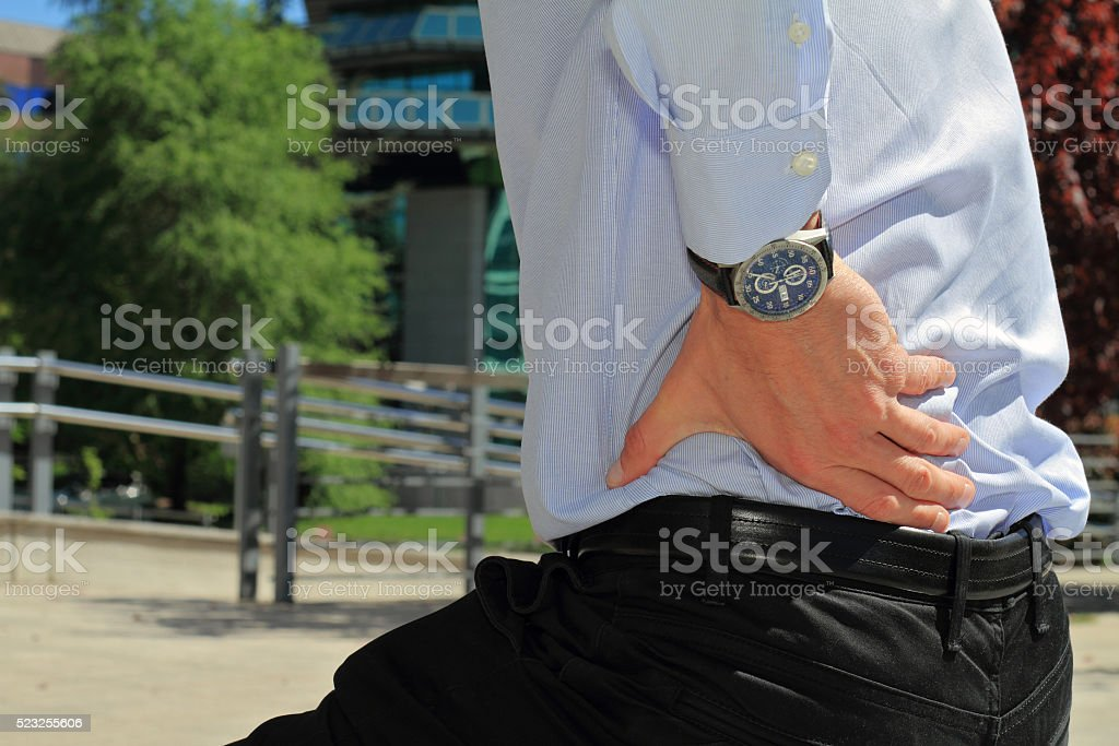 Business man holding his lower back.  Pain relief concept stock photo