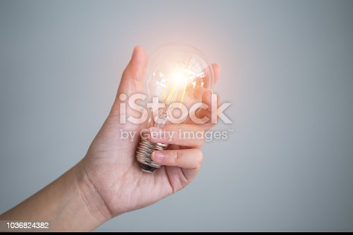 istock Business man holding light bulbs, ideas of new ideas with innovative technology and creativity. 1036824382