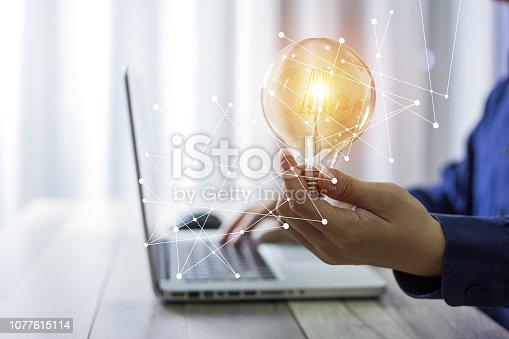 istock Business man holding light bulbs, ideas of new ideas with innovative technology and creativity. 1077615114