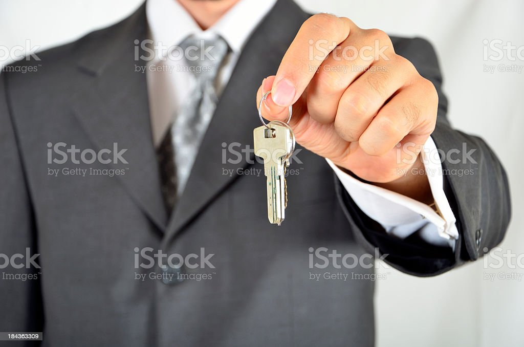 A business man holding out a key royalty-free stock photo