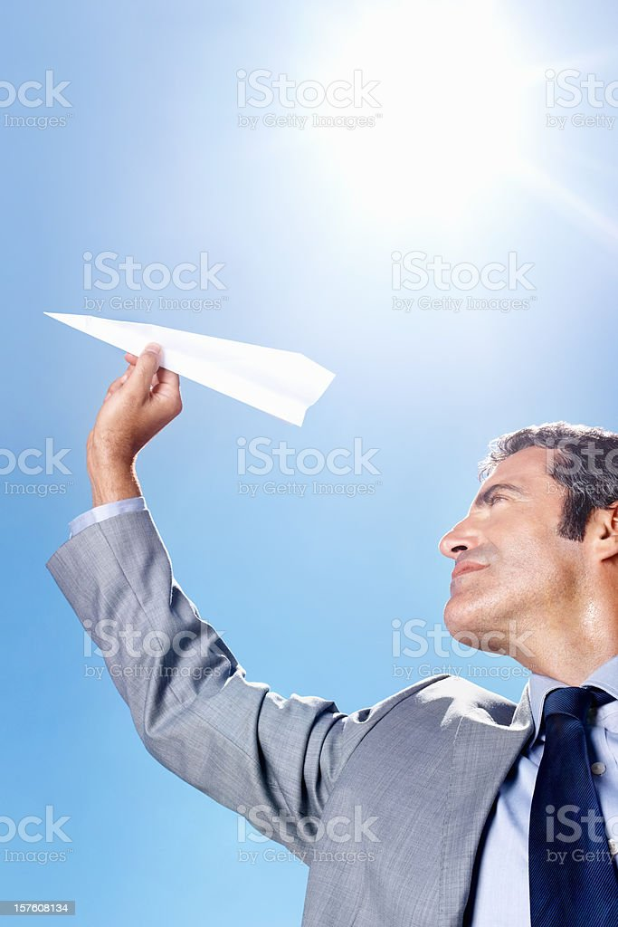Business man holding paper aircraft against blue sky royalty-free stock photo