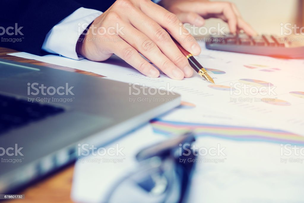 business man holding pen pointing on summary report chart stock photo
