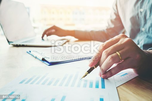 Business man holding pen pointing on summary report chart