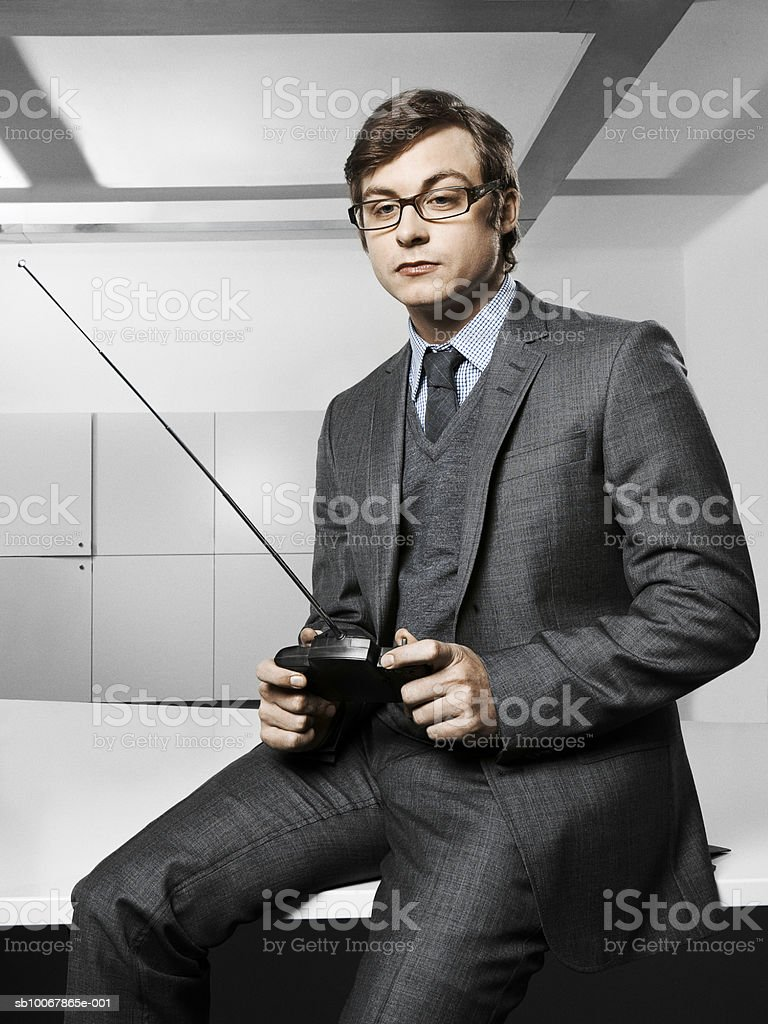 Business man holding radio control handset, sitting on desktop in office foto de stock libre de derechos