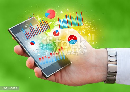 1133586715istockphoto Business man holding smartphone with chart symbols 1061404624