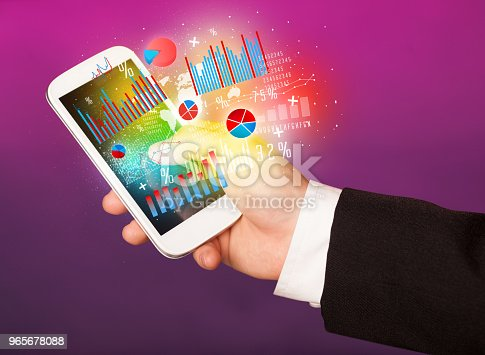 istock Business man holding smartphone with chart symbols 965678088