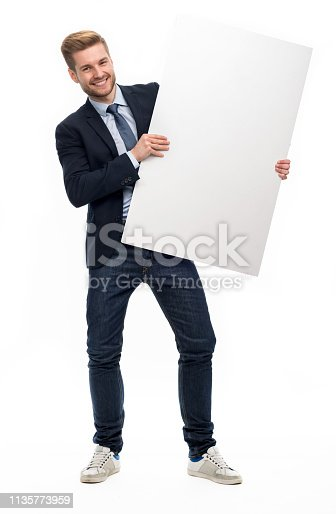 875677322istockphoto Business man holding white board 1135773959