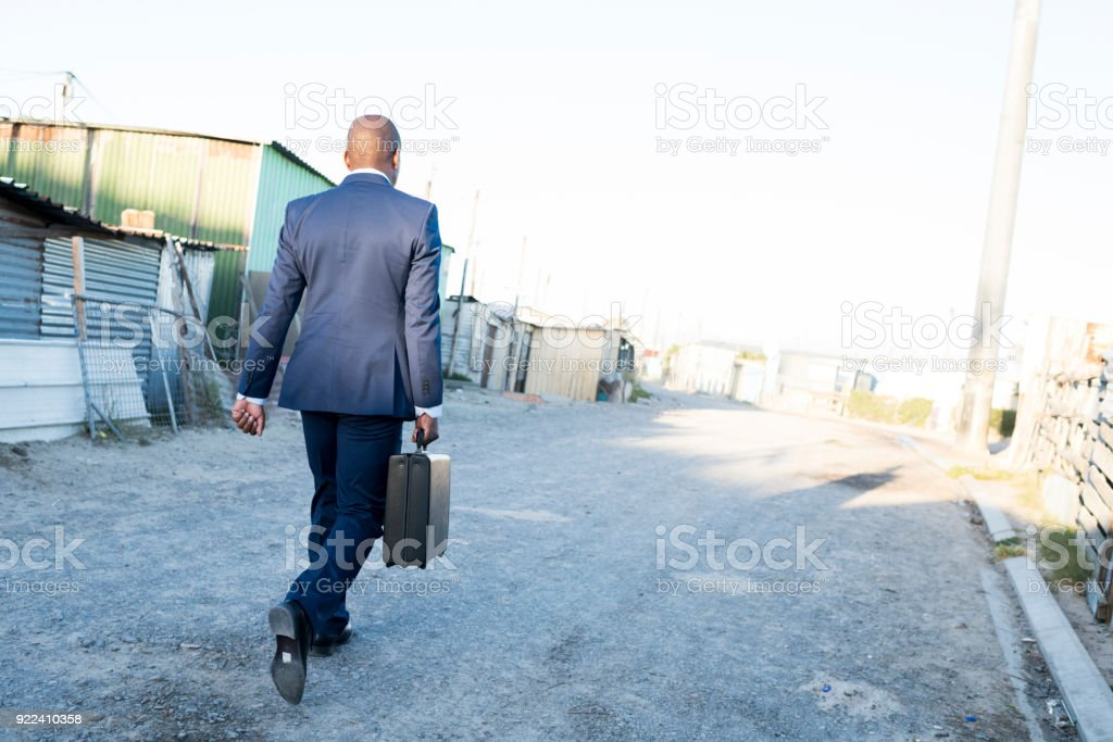 Business man in a suit walking away stock photo