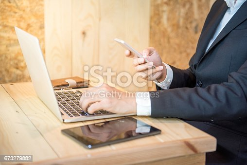 istock Business man in black suit holding smartphone and using laptop 673279882
