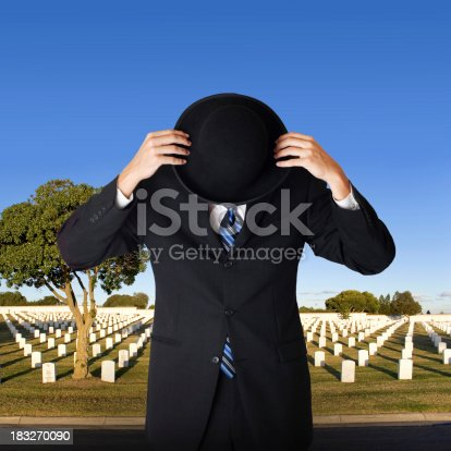 A man in a suit hides his head in his bowler hat. Cemetery in the background.Grave names are unreadable but appear to be normal names.