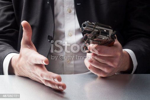 istock business man in despair with revolver 487052721