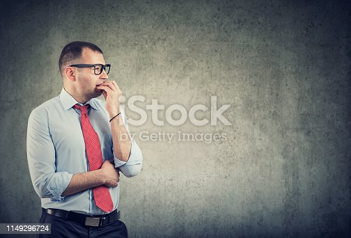 668329720 istock photo business man in glasses biting nails being in panic and anxiety looking to the side 1149296724
