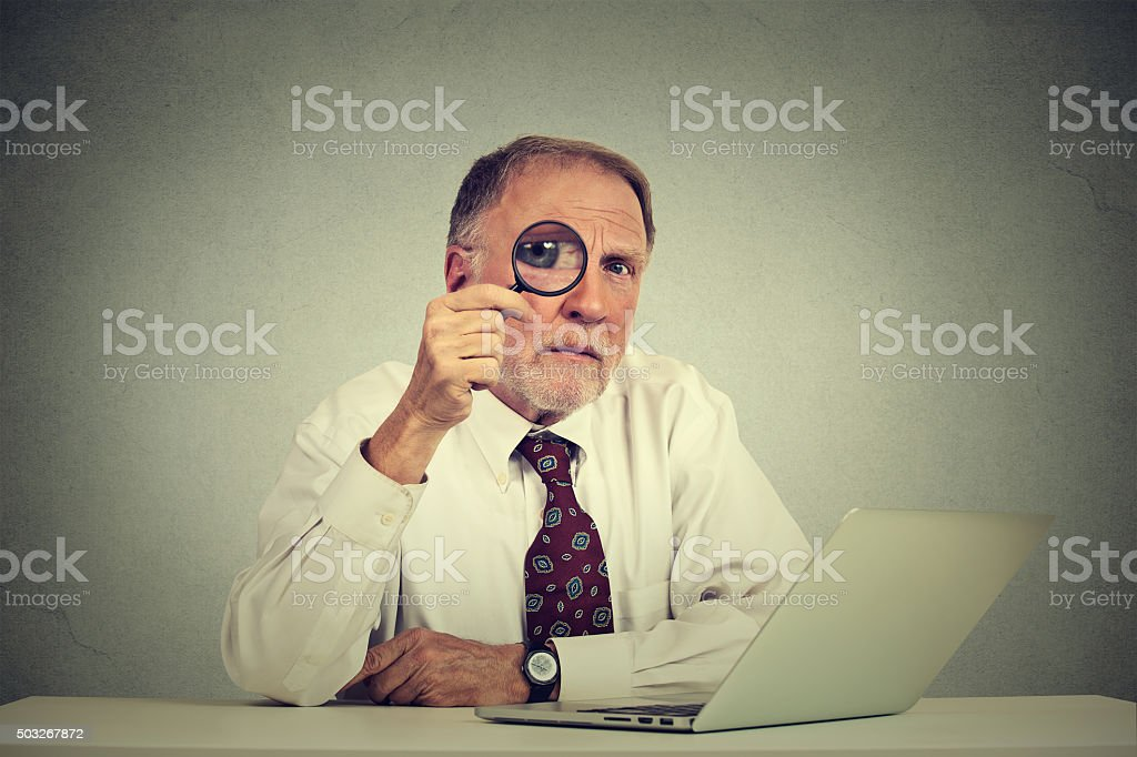 business man in glasses skeptically looking through magnifying glass stock photo