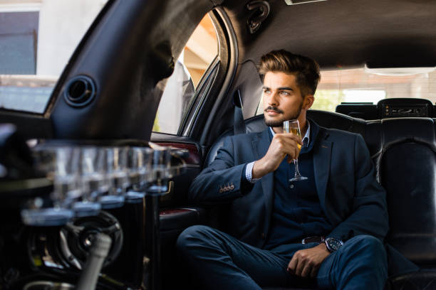 Business man in limousine with glass of champagne Business man in limousine with glass of champagne, enjoying luxury car stock pictures, royalty-free photos & images