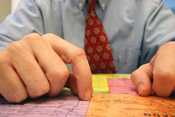Business man in red tie analyzing maps stock photo