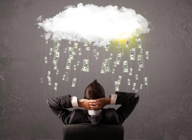 geschäftsmann im anzug blick auf wolke mit fallenden geld - bogen bauen stock-fotos und bilder