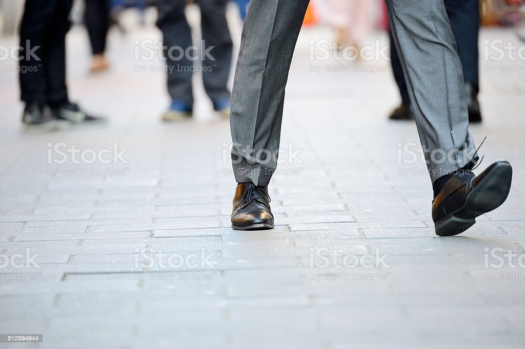 Business man in suit taking a big fast step forward stock photo