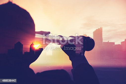 Business man in suit with cityscape montage. The man is unrecognizable and you cannot see his face. He is superimposed onto a city skyline at sunset. He is holding a telescope looking into the city. Success, vision concept with copy space.