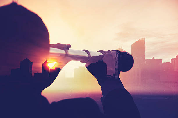 Business man in suit with cityscape montage. Business man in suit with cityscape montage. The man is unrecognizable and you cannot see his face. He is superimposed onto a city skyline at sunset. He is holding a telescope looking into the city. Success, vision concept with copy space. the way forward stock pictures, royalty-free photos & images