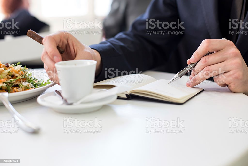 Business man indoor with coffee and healthy meal taking notes stock photo