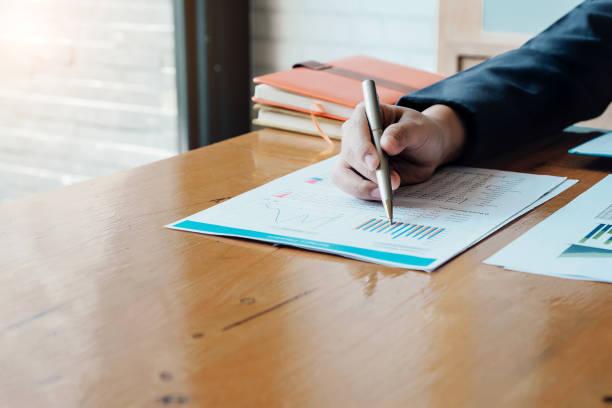 Business Man Investment Consultant analysiert die Bilanzdesatodann des Unternehmens, die mit Dokumentendiagrammen arbeitet. Konzeptbild von Geschäft, Markt, Büro, Steuer. – Foto