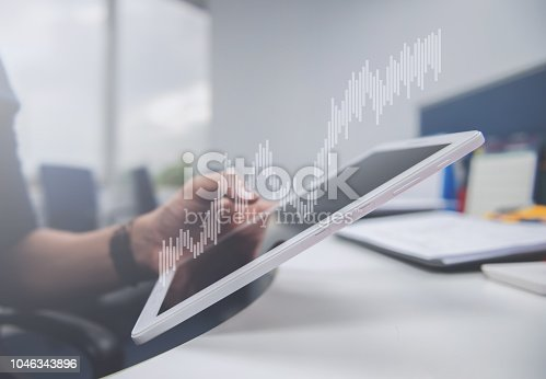 istock Business man is holding the tablet, double exposure of candlestick chart for finance and trading 1046343896