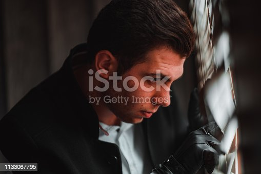 Business man is looking at the window. A mafia boss or a politician with a beard is looks angry in his hotel room. A rich man on a business trip