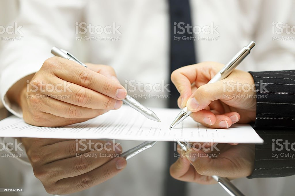 Business man is pointing woman where to sign document stock photo